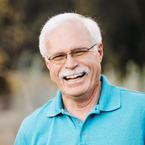 Elderly man laughing outdoors