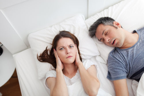 Woman laying awake and frustrated as her sleeping partner snores