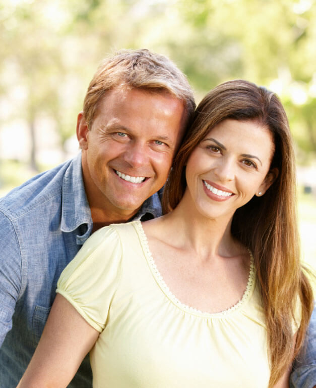 Middle-aged couple smiling outdoors