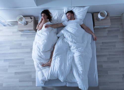 Woman awake and frustrated as her sleeping partner strecthes across the bed