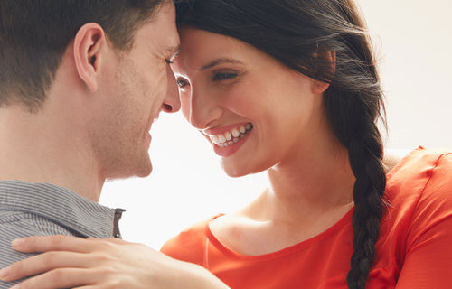 Young couple smiling and leaning towards each other